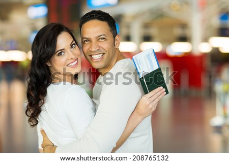 lovely couple at airport looking back - stock photo