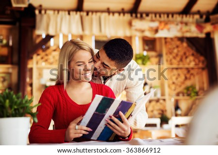 Lovely couple choosing some specialty from menu. Shallow depth of field.