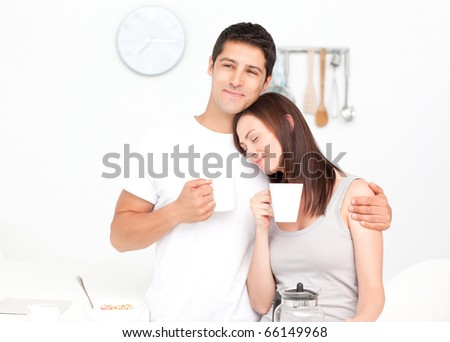 Lovely couple drinking coffee during breakfast in the kitchen