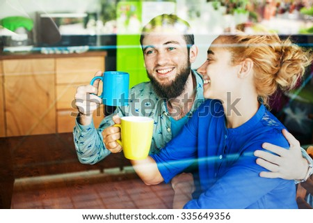 Lovely couple drinking tea together and talking. View through the glass window - stock photo