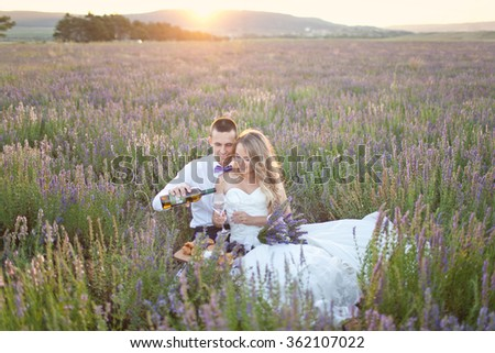 Lovely Couple drinking wine in lavender violet field. Summer mood. Wedding lovers relaxing on summer sunset - stock photo