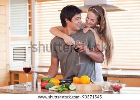 Lovely couple drinking wine while hugging in their kitchen - stock photo