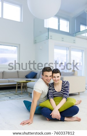 Lovely couple enjoying free time sitting on the floor in their living room at home