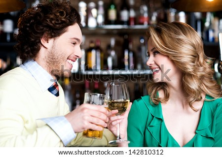 Lovely couple enjoying their drinks together - stock photo
