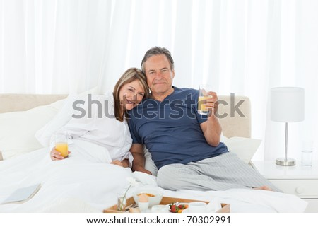 Lovely couple  having breakfast in their bed at home - stock photo