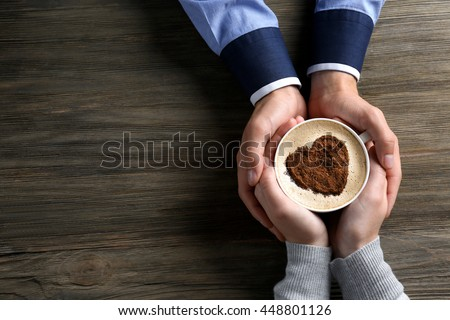Lovely couple holding cup of coffee in hands on wooden background - stock photo