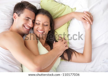 Lovely couple hugging on their bed at home - stock photo