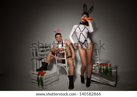 Lovely couple in rabbit costumes with carrots - stock photo
