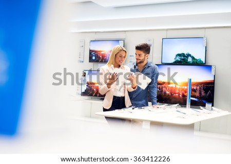 Lovely couple is at store and they are looking for a new mobile, tablet or TV at catalog. Shallow depth of field. - stock photo