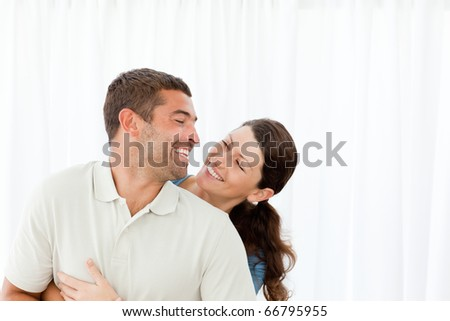 Lovely couple laughing together in the living room at home - stock photo