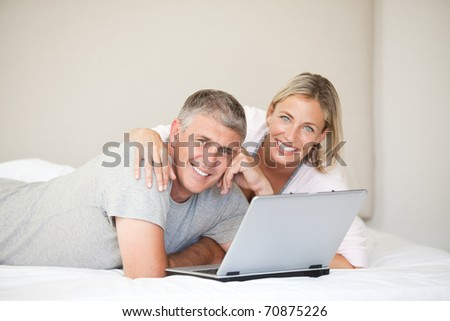 Lovely couple looking at the camera at home - stock photo
