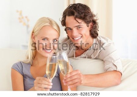 Lovely couple making a toast while looking at the camera