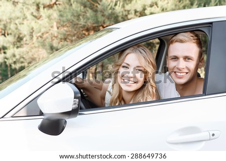 Lovely couple. Portrait of a young beautiful blond woman with curvy hair and her handsome boyfriend sitting in a car near to each other looking out of the window smiling happily - stock photo