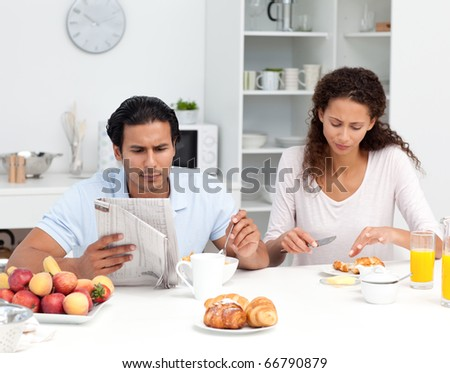 Lovely couple reading the newspaper while having breakfast in kitchen - stock photo