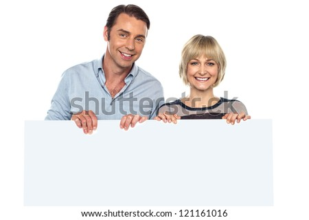 Lovely couple standing behind blank billboard, smiling and looking at the camera. - stock photo