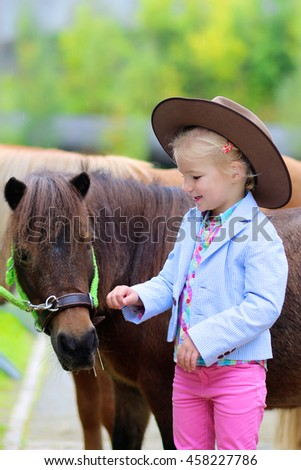 Lovely cowgirl caressing little pony horse in the farm. Pretty preschooler girl wearing cowboy hat playing with animals outdoors on sunny day. - stock photo