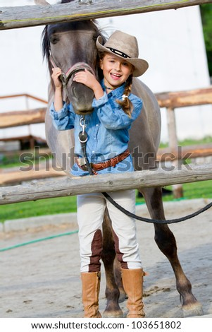 Lovely cowgirl with horse on a ranch - stock photo