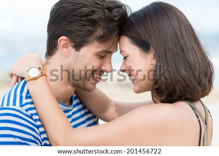 Lovely cuddling couple touching foreheads standing close to each other