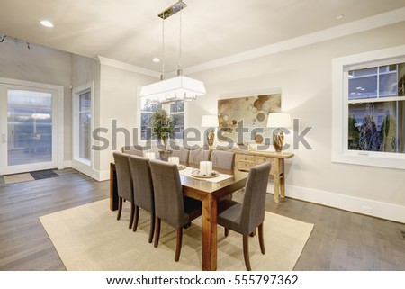 Lovely dining room with rectangular dining table paired with grey high back dining chairs over sisal rug. Northwest, USA