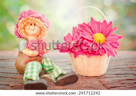 Lovely doll sitting and flowers in a Basket on a wooden with bokeh background in a vintage retro style, with the sunrise, for the day of love, Valentine's Day. - stock photo