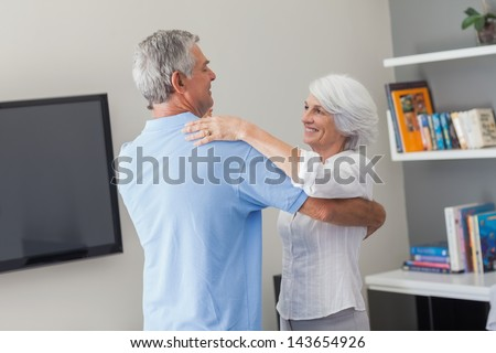 Lovely elderly couple dancing in their living room - stock photo