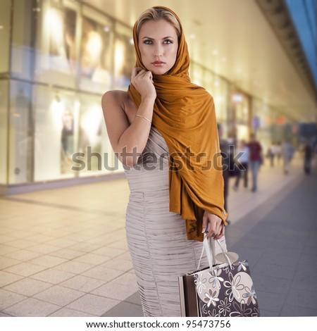 lovely elegant lady with orange scarf and shopping bag over white - stock photo
