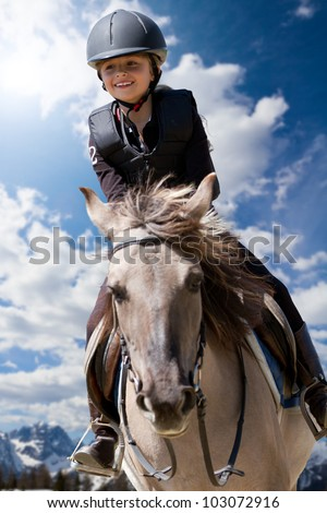 Lovely equestrian - little girl is riding a horse, Dolomites mountain in the background - stock photo