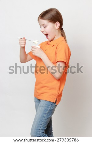 Lovely european little girl eating yoghurt - stock photo