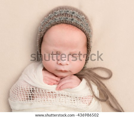 lovely face of sleepy swaddled newborn baby in knitted hat - stock photo