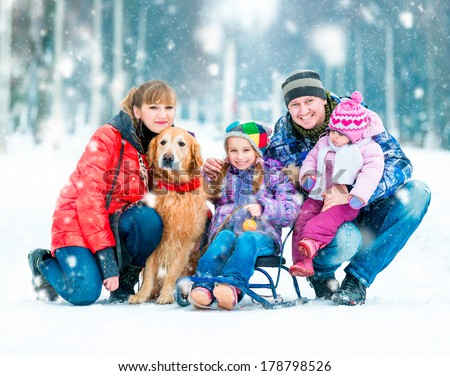 lovely family: father, mother, two daughters and dog in winter park - stock photo