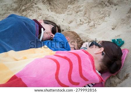 lovely family sleeping on the beach - stock photo