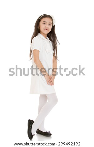 Lovely fashion small girl Oriental appearance with long dark hair on the head and the rim that holds the hair in a short white dress and white tights smiles sweetly at the camera with folded hands in - stock photo
