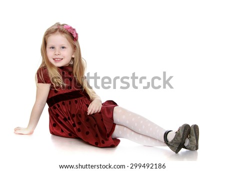 Lovely fashion small girl with long white hair on my head and a headband that keeps hair in long brown polka dot dress and white tights smiles sweetly at the camera , girl sitting on the floor with - stock photo