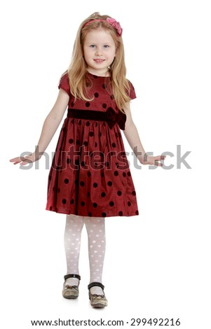 Lovely fashion small girl with long white hair on my head and a headband that keeps hair in long brown polka dot dress and white tights smiles sweetly into the camera to place in the palm of your - stock photo