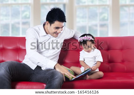 Lovely father reading story book with his baby at home - stock photo