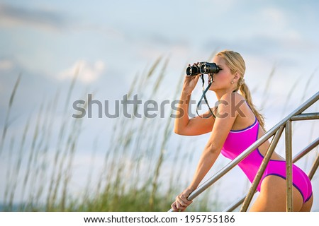 lovely female in pink one-piece swimsuit scans the ocean with binoculars at a florida beach - stock photo