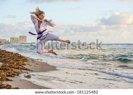 lovely female jujitsu expert practicing kick at the beach - stock photo