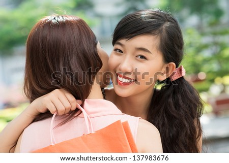 Lovely friends hugging being glad about their successful shopping - stock photo