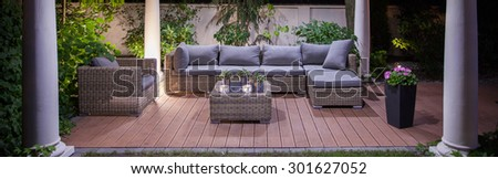 Lovely garden patio with cozy wicker furniture - stock photo