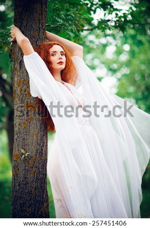 Lovely ginger woman wearing white dress stands near the tree - stock photo