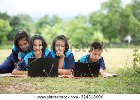 lovely girl and boy friend study computer on grass happy and smile - stock photo
