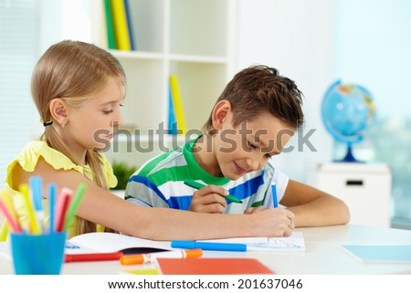 Lovely girl and her classmate drawing together at lesson - stock photo