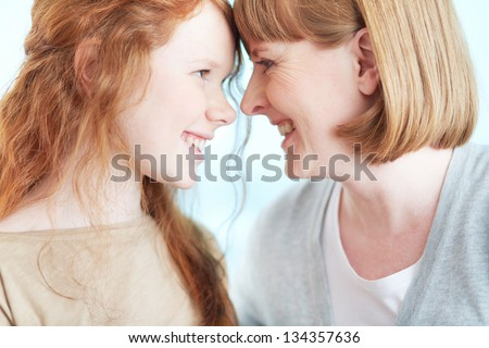 Lovely girl and her mother looking at one another with smiles - stock photo