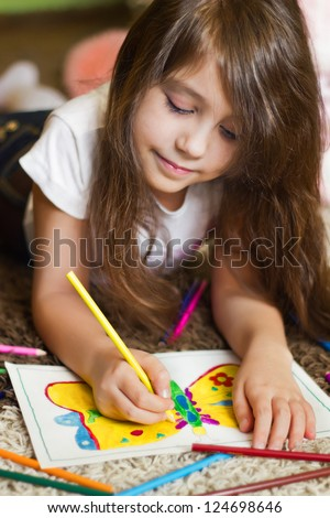 Lovely girl drawing a picture with colorful pencils