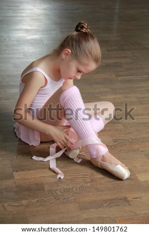 Lovely girl engaged in a pink ballet tutu and pointes in the ballet hall on the wooden dance floor - stock photo