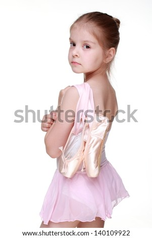 Lovely girl holding ballet shoes (pointes)