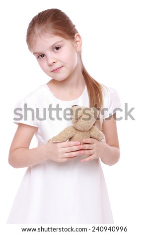 Lovely girl in a beautiful holiday dress holding a small teddy bear isolated on white