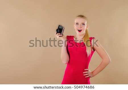 Lovely girl in a bright dress takes pictures old photo camera