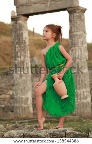 Lovely girl in a bright dress with vintage antique amphora on the excavation of the ancient city - stock photo