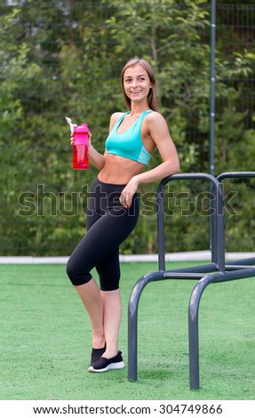 Lovely girl in sportswear with a bottle of water smiling on the playground. - stock photo